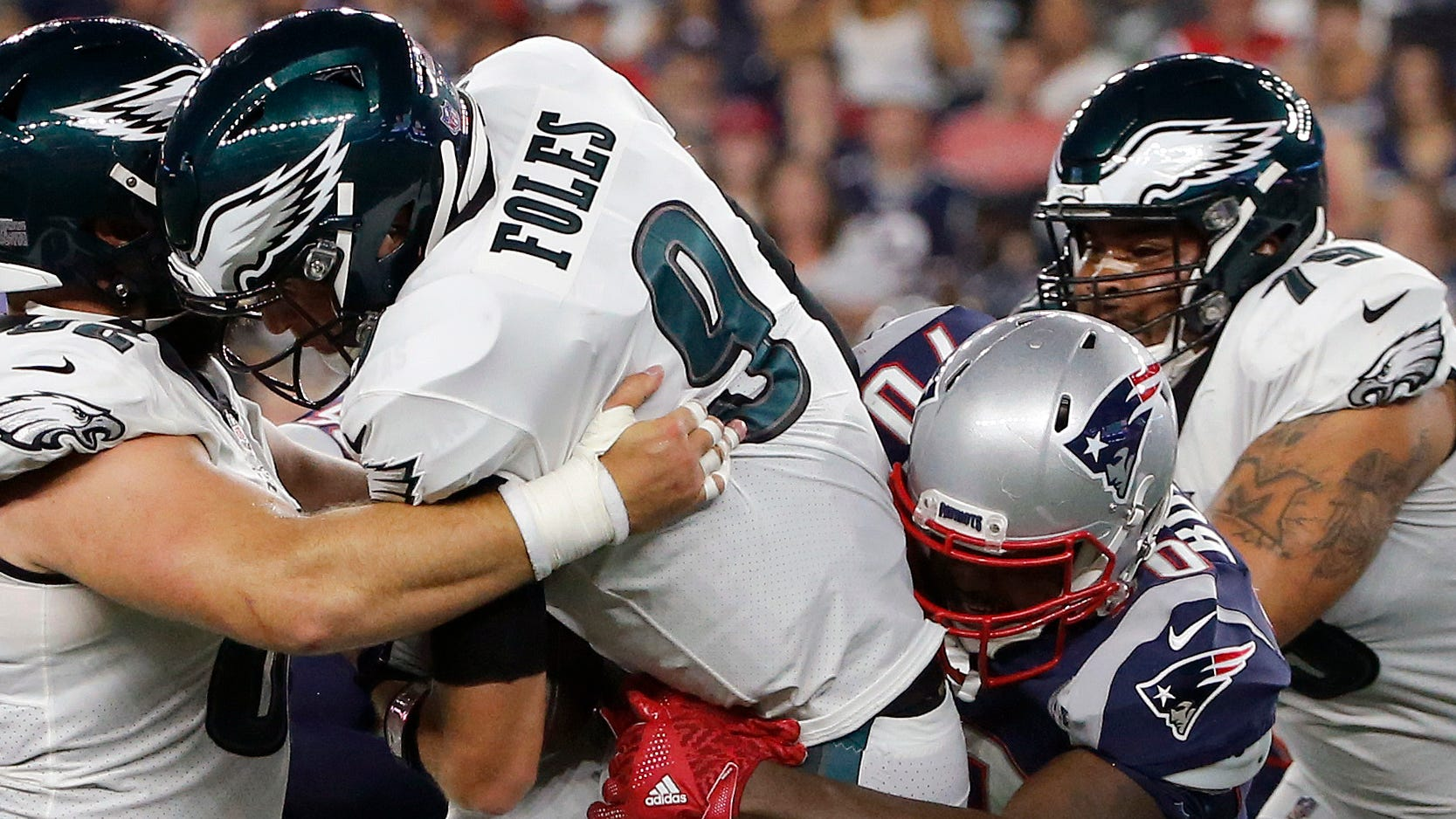 New England Patriots defensive tackle Adam Butler, right, sacks Philadelphia Eagles quarterback Nick Foles during the first half of a preseason NFL football game, Thursday, Aug. 16, 2018, in Foxborough, Mass. (AP Photo/Mary Schwalm)