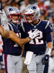 New England Patriots quarterback Tom Brady (12) talks to receiver Chris Hogan, left, during the first half of a preseason NFL football game against the Philadelphia Eagles, Thursday, Aug. 16, 2018, in Foxborough, Mass. (AP Photo/Mary Schwalm)