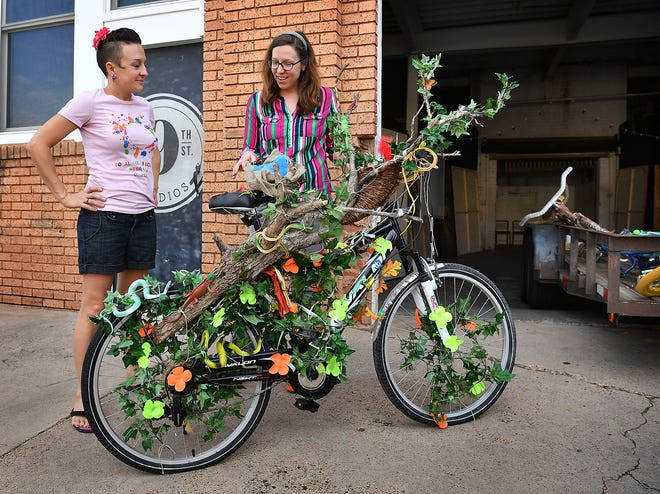 Teaching artists Amber Scott, left, and Audra Lambert check out an Art Bike creation from River Bend Nature Center as the bicycles are being moved for display at Sikes Senter Mall.
