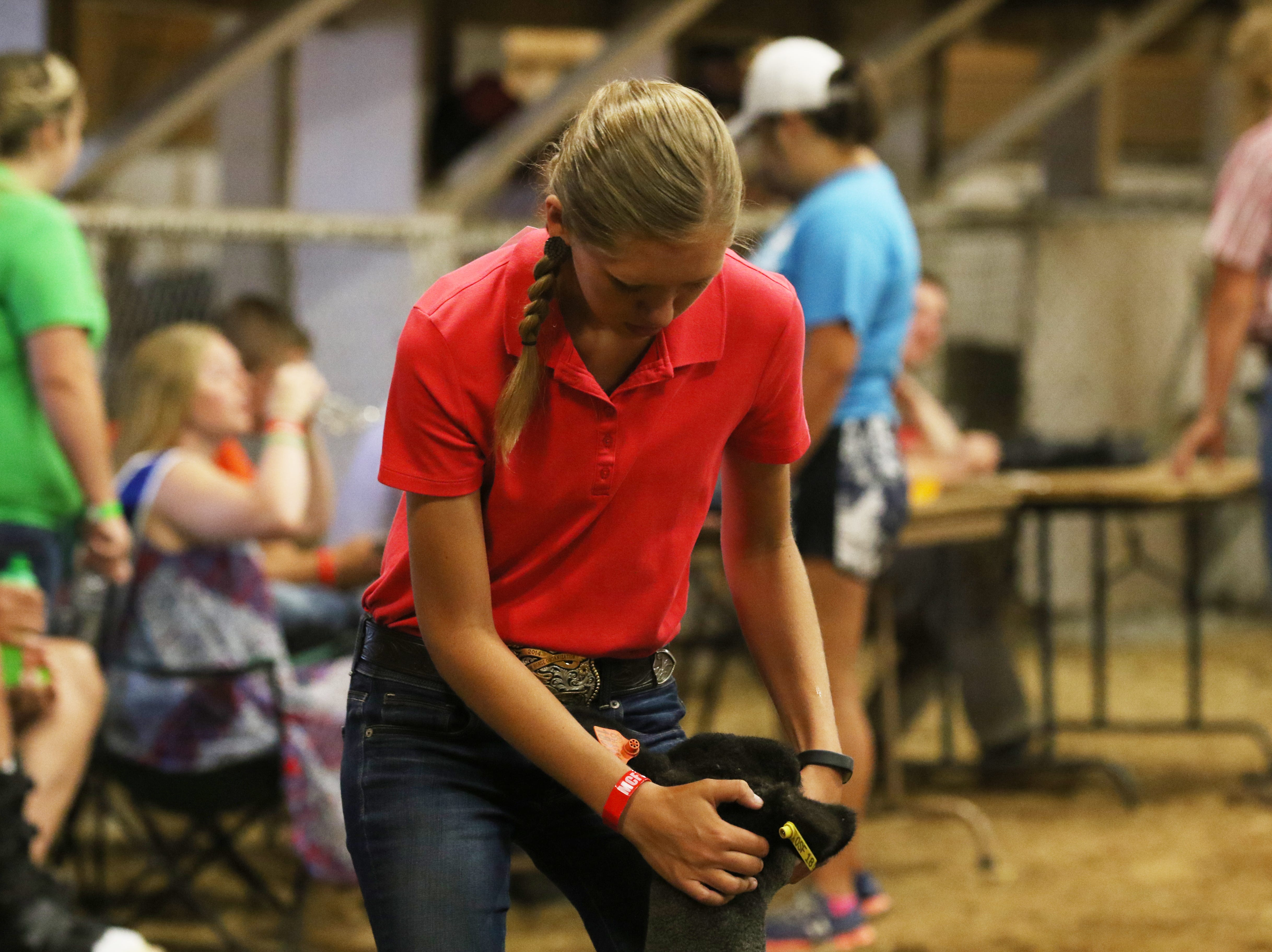 Camryn Caplinger shows a lamb during the Showman of Showmen competition at the Muskingum County Fair on Friday.
