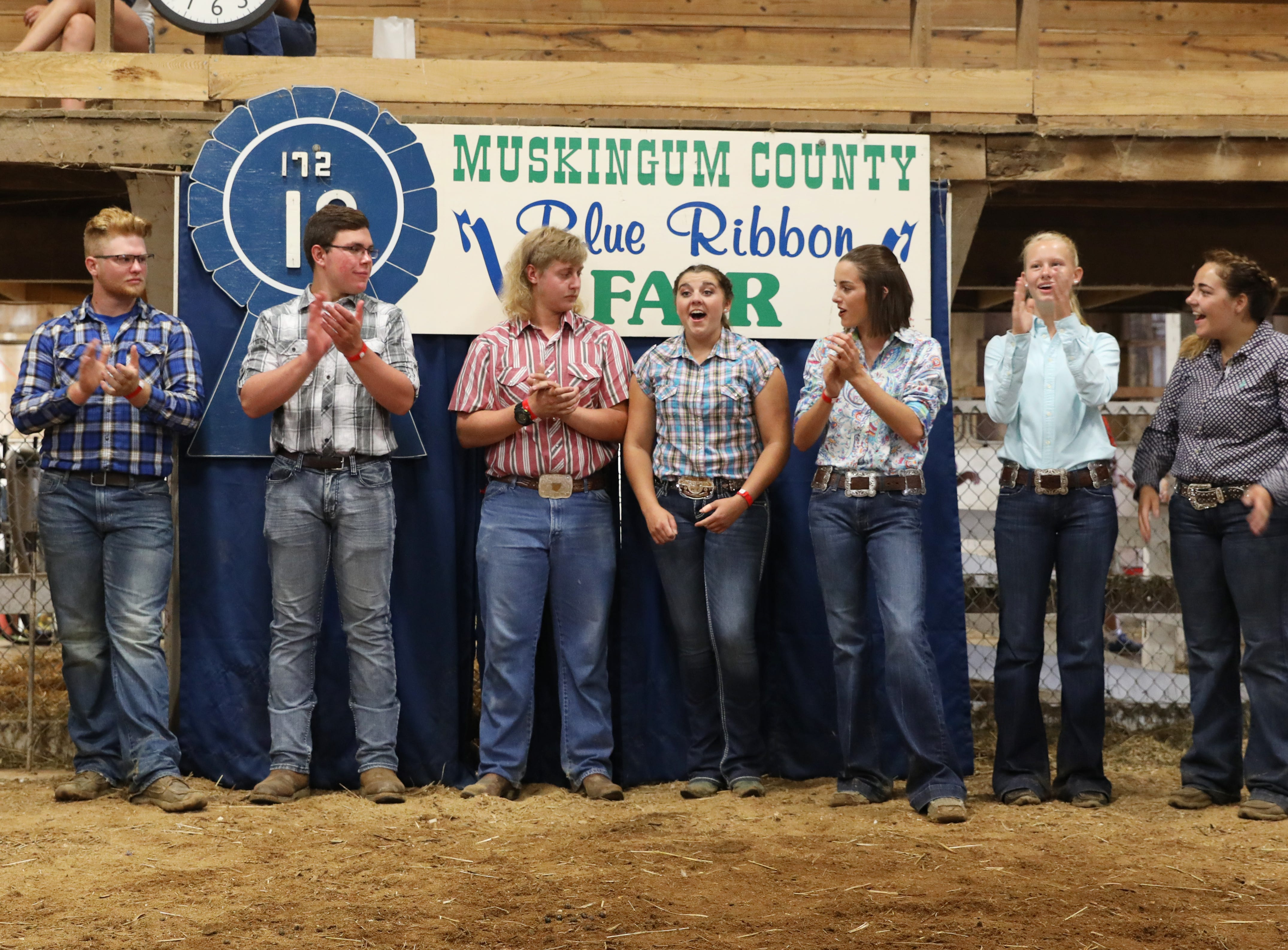 Class winners applaud as Jaylee Jordan is announced as Champion of Champions at the Muskingum County Fair on Friday. From left, the champions are Tyler McKenzie, Adam Crock, Tom Mozena, Jordan, Hainsley Hatfield, Kamryn Kreis and Brielle Vernon. Not pictured is Camryn Caplinger. For more photos visit www.zanesvilletimesrecorder.com.