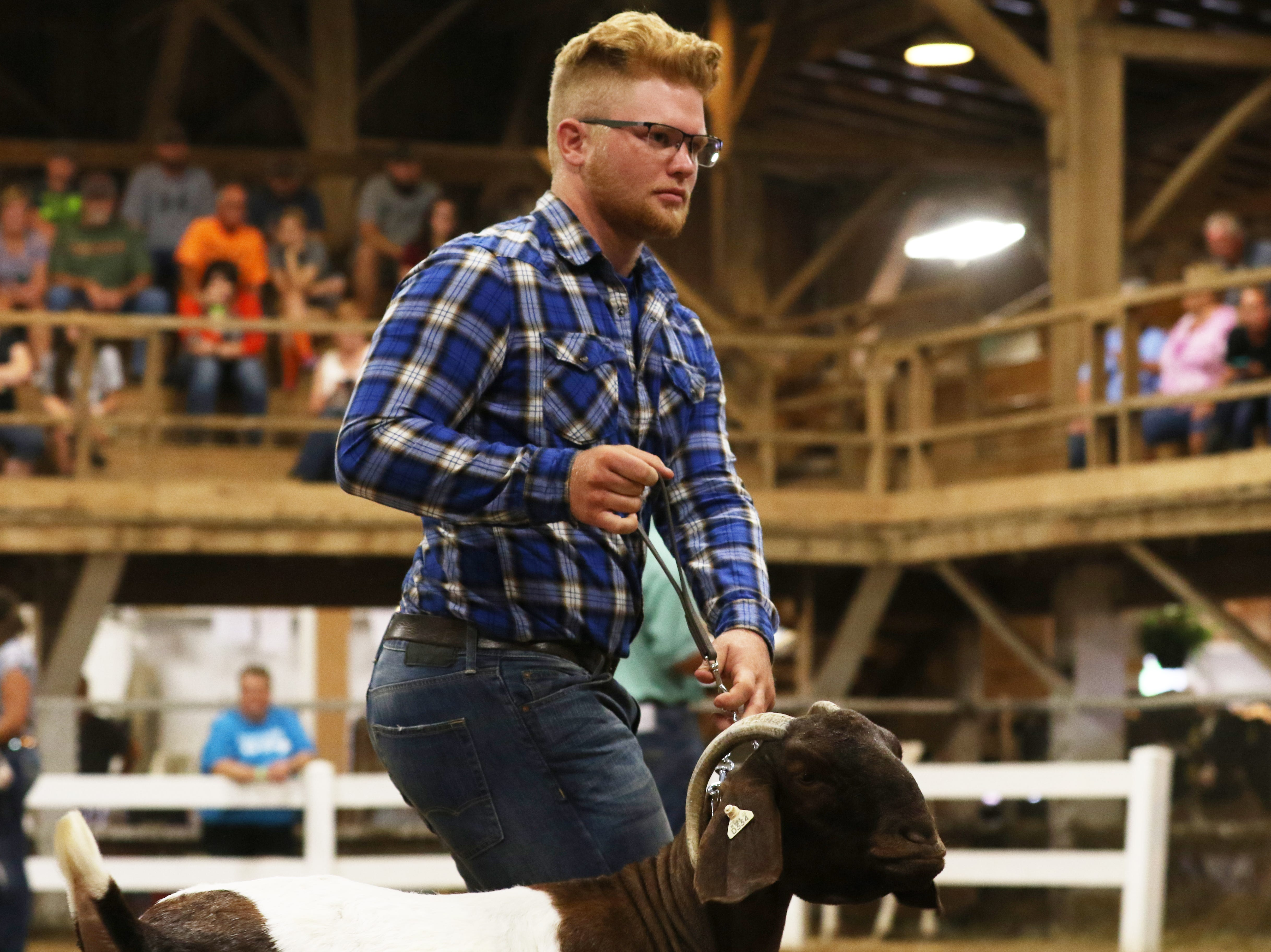 Tyler McKenzie shows a goat during the Showman of Showmen competition at the Muskingum County Fair on Friday.