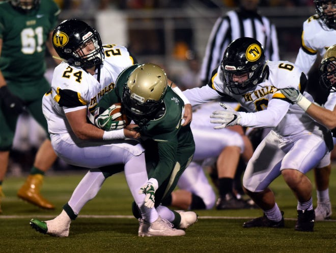 Tri-Valley's Chase Kendrick (24) and Greg Nolder tackle Terrance Keyes during Tri-Valley's win against Akron St. Vincent-St. Mary last season. Kendrick is one of several seniors returning from the state runner-up squad, which is now led by coach Kevin Fell.