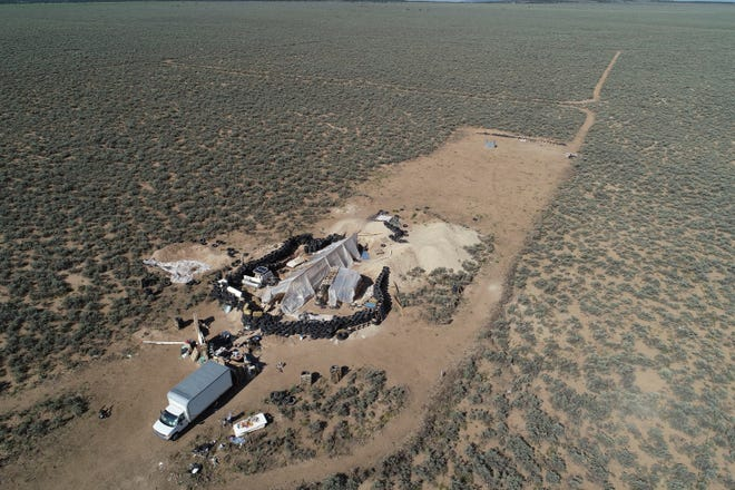 In this Aug. 10, 2018 file photo aerial view of a makeshift compound is seen in the desert area of Amalia, New Mexico. Forensic investigators announced Aug. 16, that a highly decomposed body found at a desert compound in New Mexico has been identified as a missing Georgia boy whose father is accused of kidnapping him and performing purification rituals on the severely disabled child.