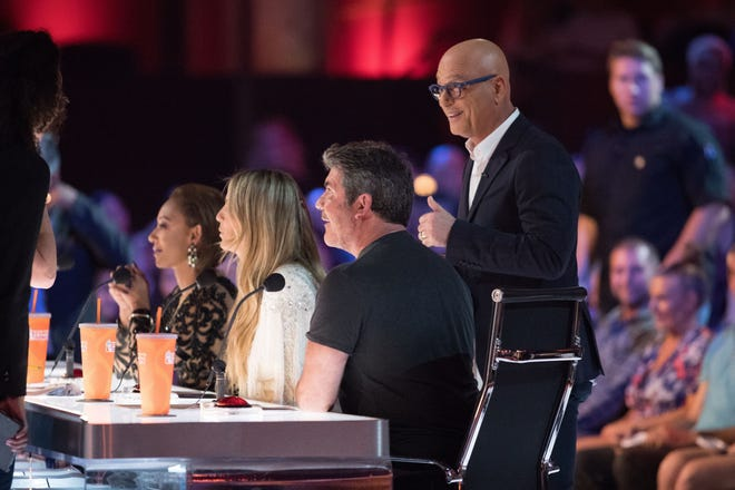 'America's Got Talent' judges Mel B, left, Heidi Klum, Simon Cowell and Howie Mandel, standing, get ready for the start of a recent live show.
