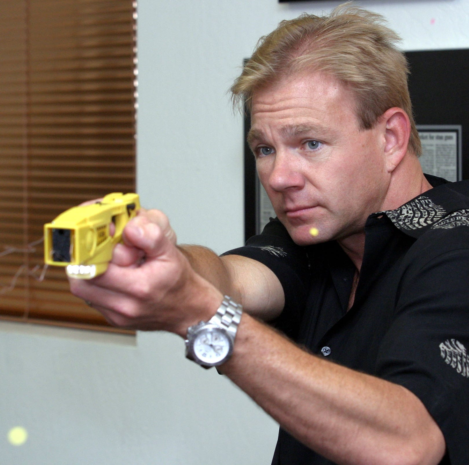 Steve Tuttle fires the Taser X-26 model, in Scottsdale, Ariz. in this 2004 file photo.