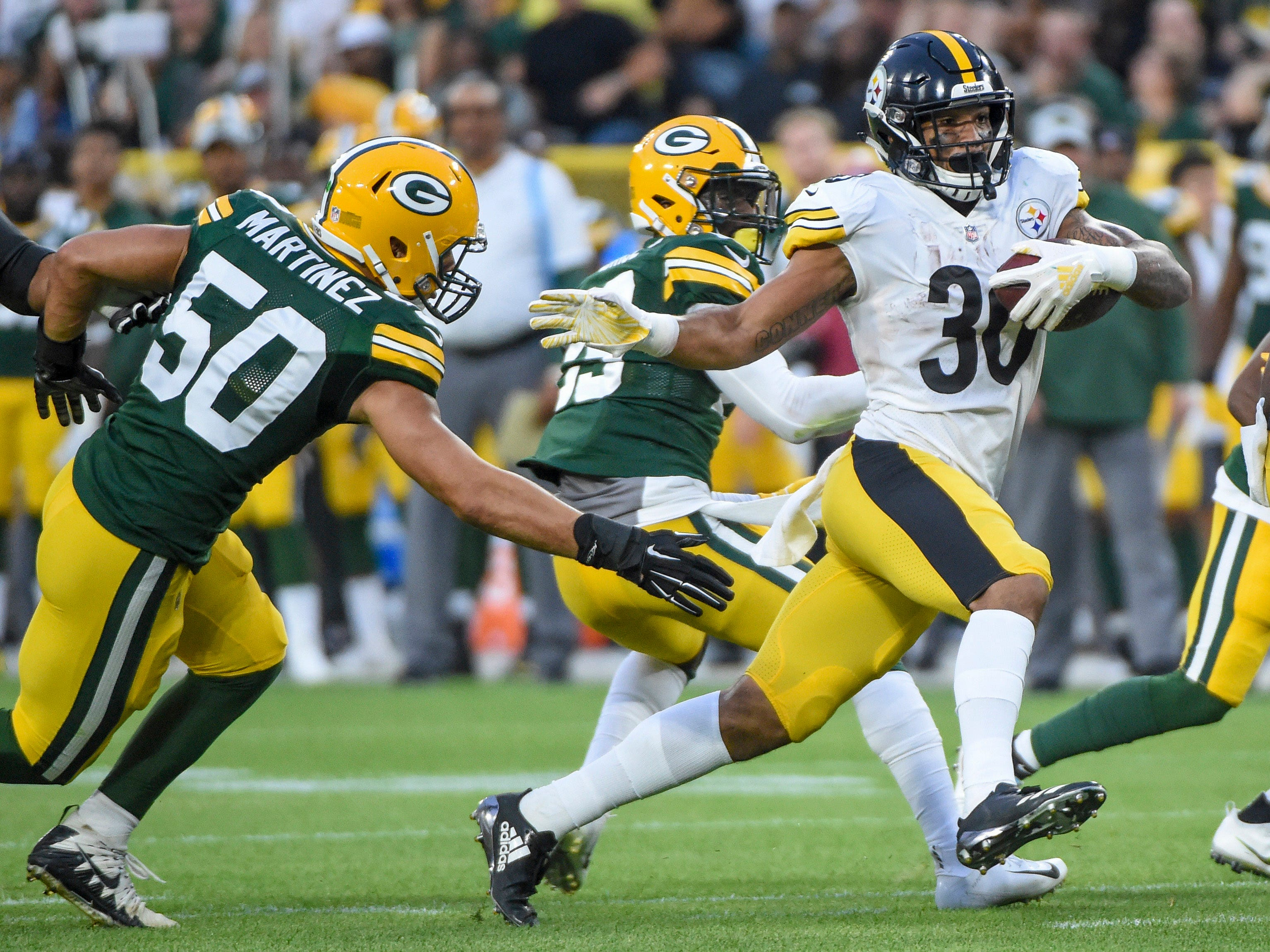 Pittsburgh Steelers running back James Conner gets past Green Bay Packers linebacker Blake Martinez to score a touchdown in the first quarter at Lambeau Field.