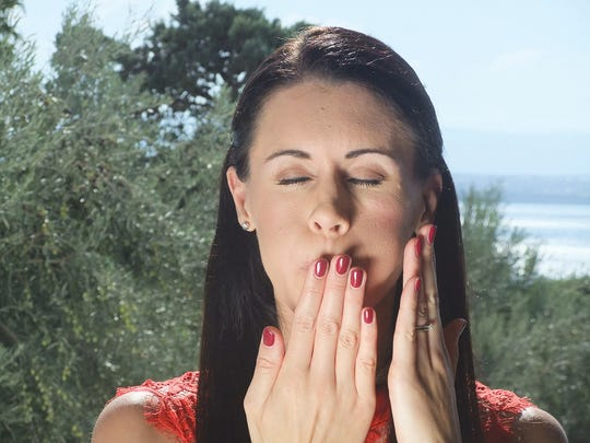 Danielle Collins demonstrates the Advanced Pufferfish facial yoga exercise.