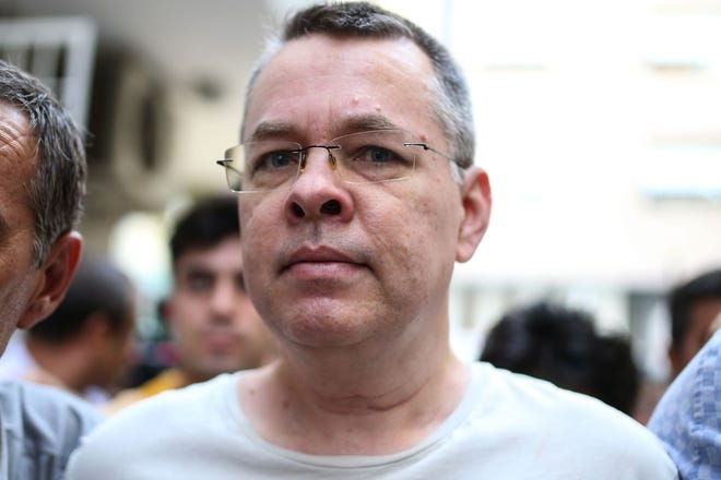In this file photograph taken on July 25, 2018, U.S. pastor Andrew Craig Brunson is escorted by Turkish plain clothes police officers to his house in Izmir. A Turkish court on Aug. 17, 2018, rejected an appeal for his release on charges of links to groups opposed to the government.