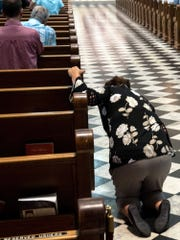 A women prays before leaving St. Patrick Cathedral in Harrisburg, Pennsylvania, following a Mass of Forgiveness on Aug. 17, 2018.