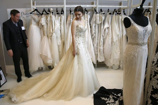 A woman tries on a wedding dress at a stand at the Paris Bridal Fair, an international bridal fashion trade show in Paris in April 2016.