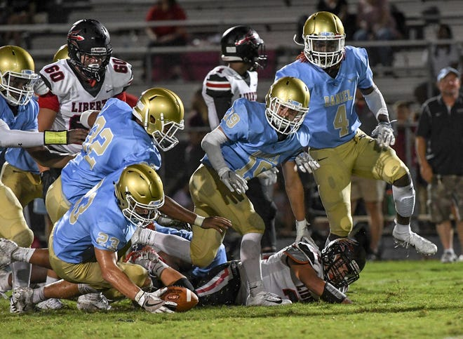 Liberty senior JT Howard(35) fumbles before DW Daniel linebacker Matthew Maloney(23) recovers during the fourth quarter at DW Daniel High School on Friday, August 17, 2018.