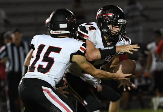 Liberty junior Carter Smith(15) hands off to Liberty senior Clay Lollis(44) during the fourth quarter at DW Daniel High School on Friday, August 17, 2018.
