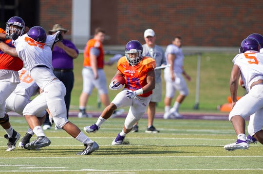 NSU running back Stadford Anderson (13) looks for a hole during the Demons second intrasquad game Saturday.