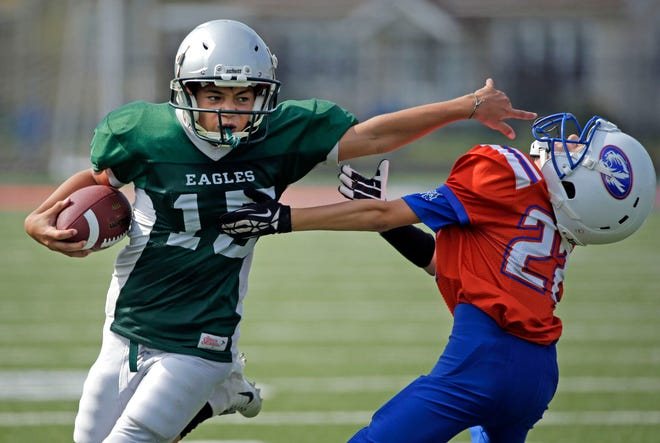 Hunter Gruse of the Oshkosh North Eagles, left, works to get around Tyce Scheetz of the Appleton West Tigers as the seventh grade teams compete in the Wisconsin Gridiron Kickoff Challenge on Saturday at Appleton West.