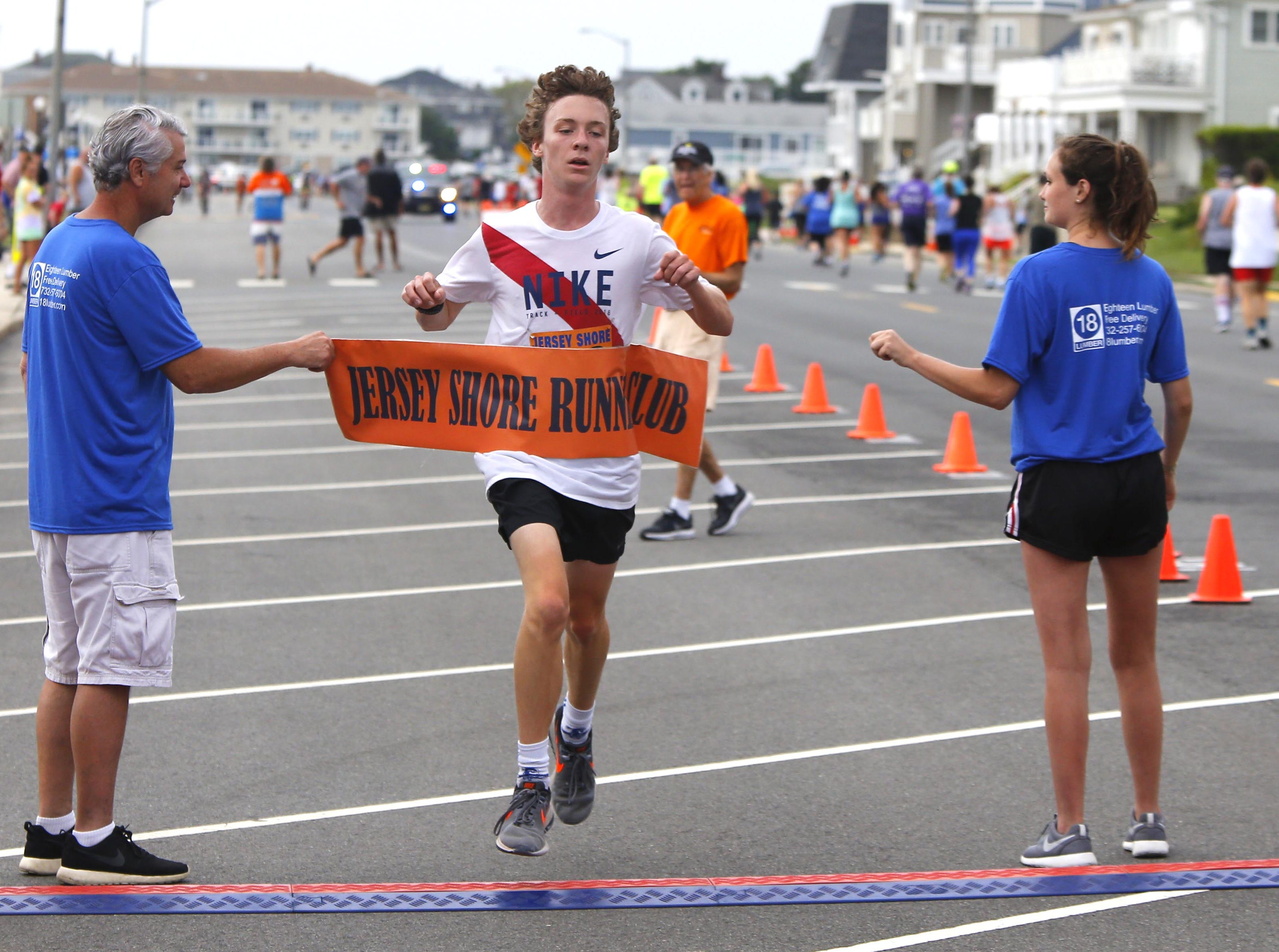 Colin Flood of Manasquan crosses finish line to win first place (male) in the Bradley Beach 5K race Saturday, Aug. 17, 2018.