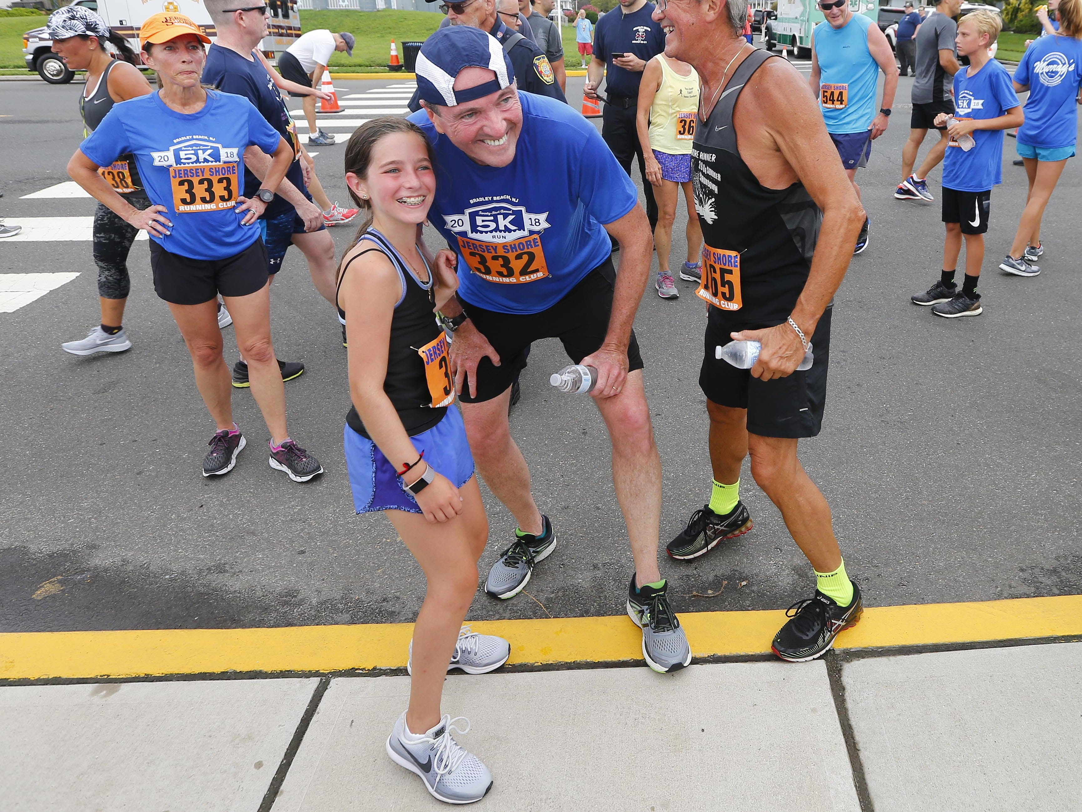 NJ Gov. Phil Murphy takes a photo with runner Lexie Berggrun, 12, of New York, after the Bradley Beach 5K race Saturday, Aug. 17, 2018.