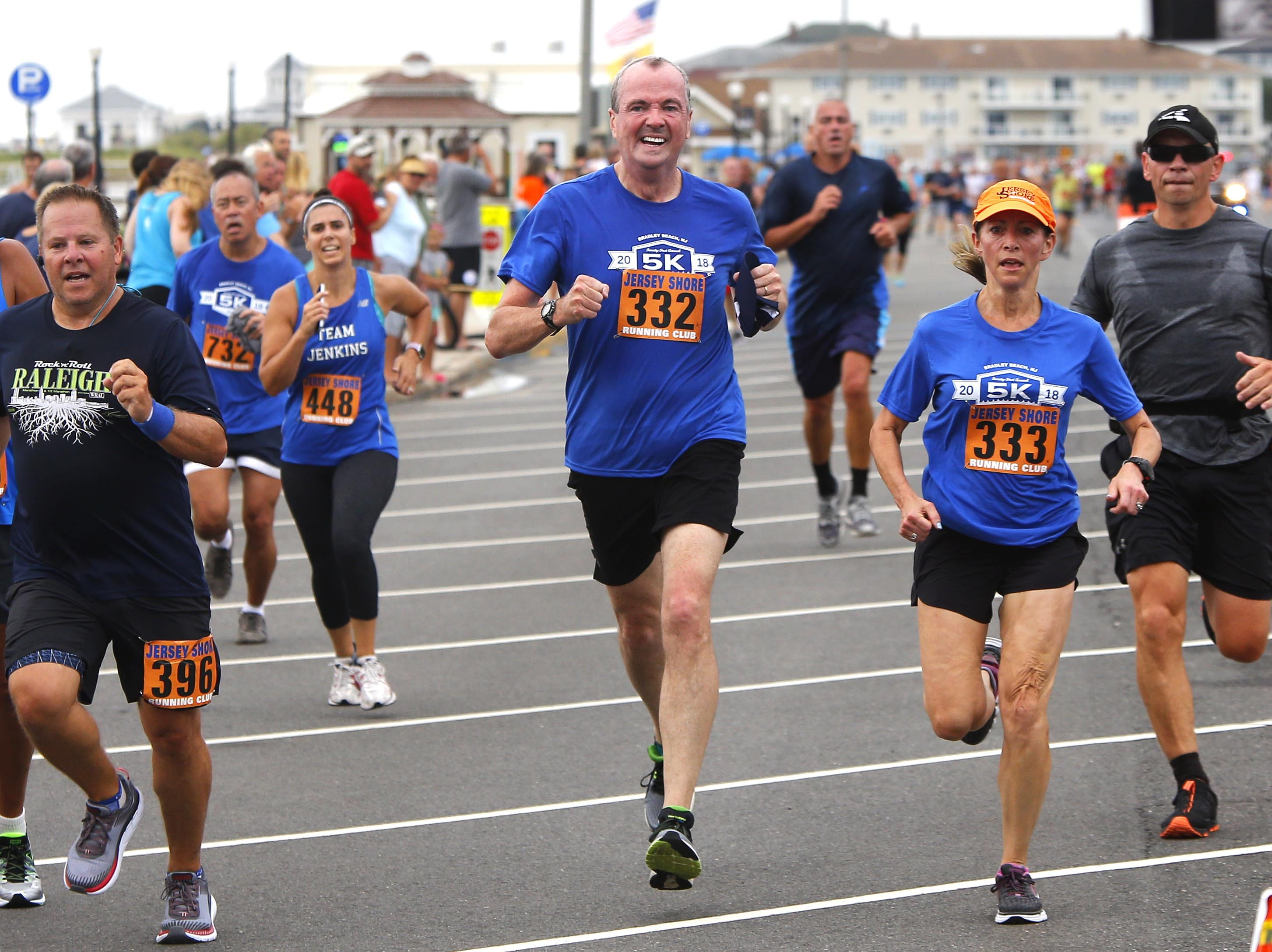 NJ Gov. Phil Murphy (center) approaches the finish line for the Bradley Beach 5K race Saturday, Aug. 17, 2018.