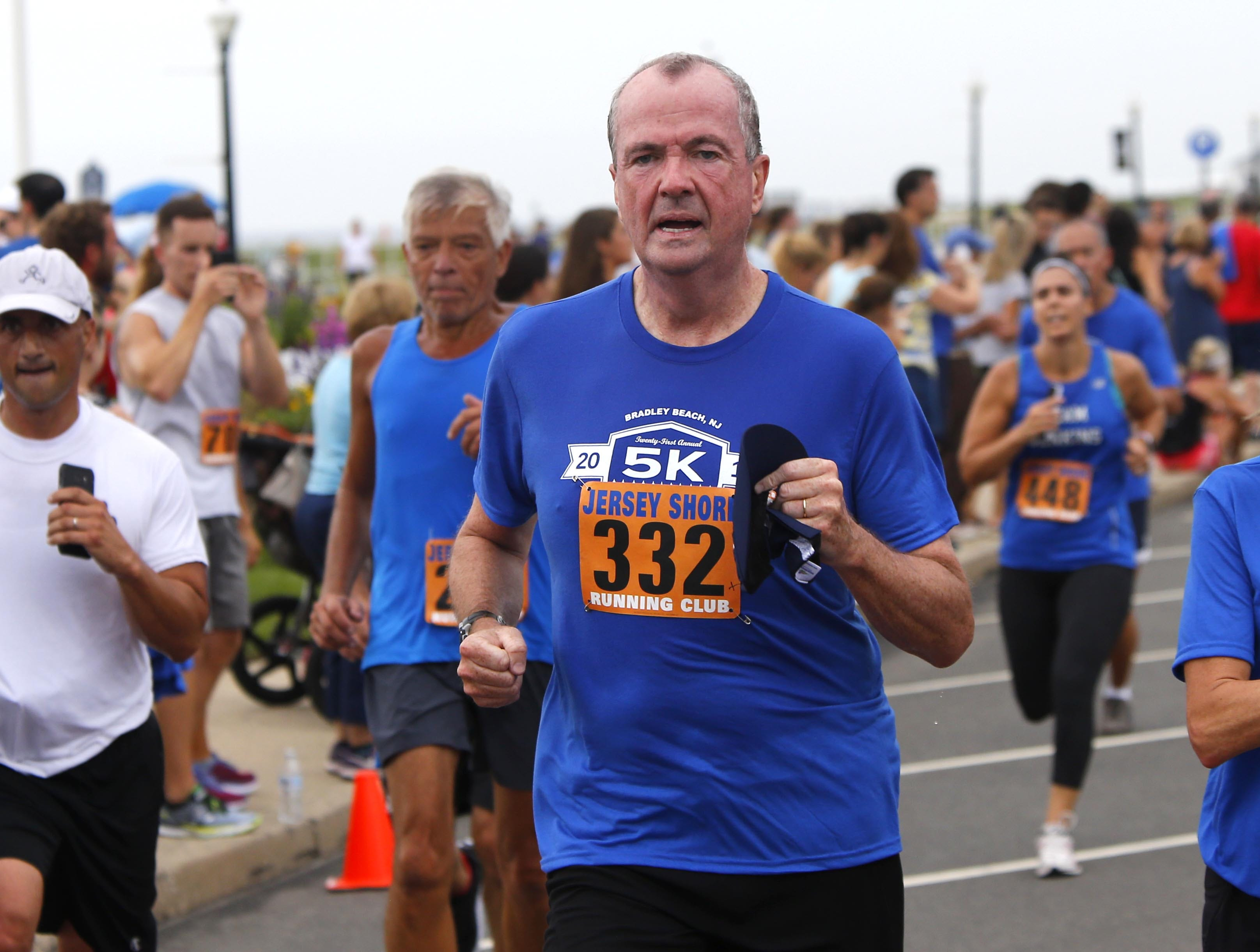 NJ Gov. Phil Murphy approaches the finish line for the Bradley Beach 5K race Saturday, Aug. 17, 2018.