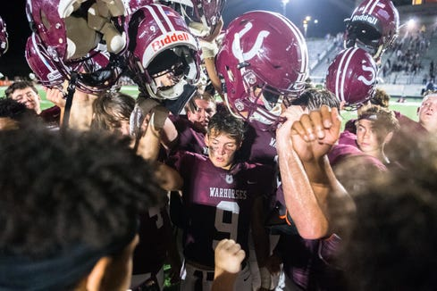 Owen's Shavoy Harding celebrates a Warhorse 34-7 victory over Enka with his teammates in their opening game of the 2018 football season.