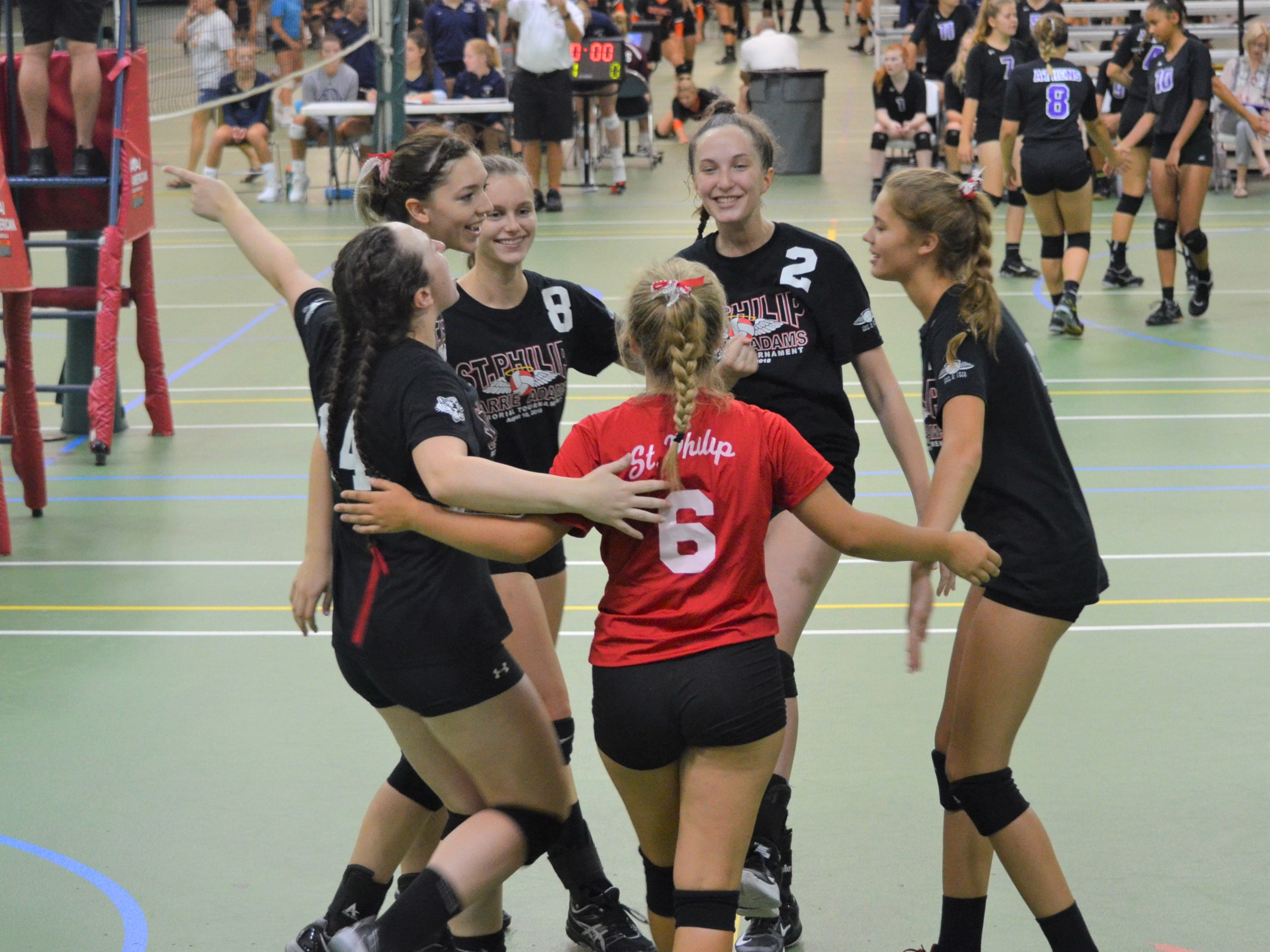 St. Philip players celebrate a point during the first weekend of the volleyball season at the Carrie Adams Memorial Tournament in Battle Creek on Saturday.