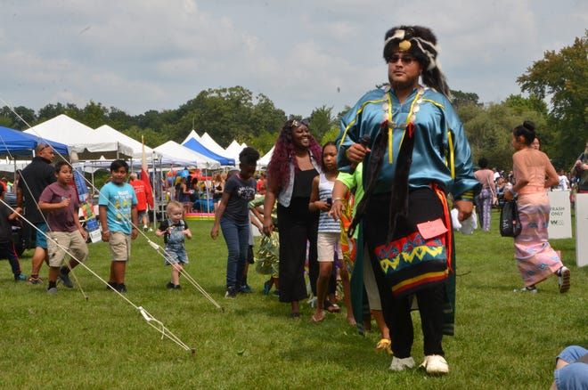 A tribal member of the Nottawaseppi Huron Band of Potawatomi wears regalia as leads audience members in a dance at the International SummerFest at Bailey Park on August 18, 2018.