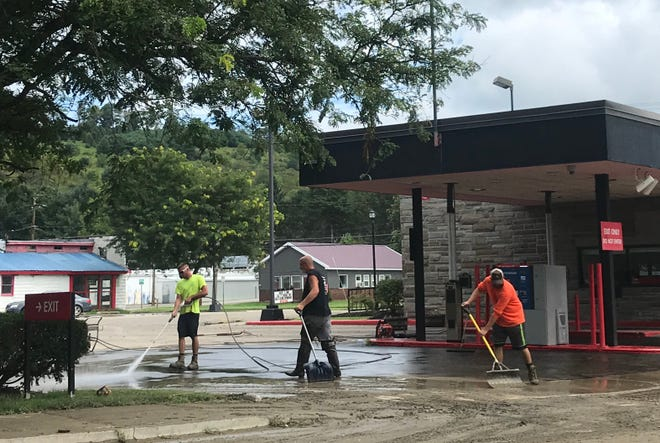 Crews clean up mud and debris from the parking lot of NBT Bank in Newark Valley on Saturday, August 18, 2018. The areas of Main and Water streets experienced flash flooding on Saturday morning after a heavy rainfall caused Oswego Creek to flood.