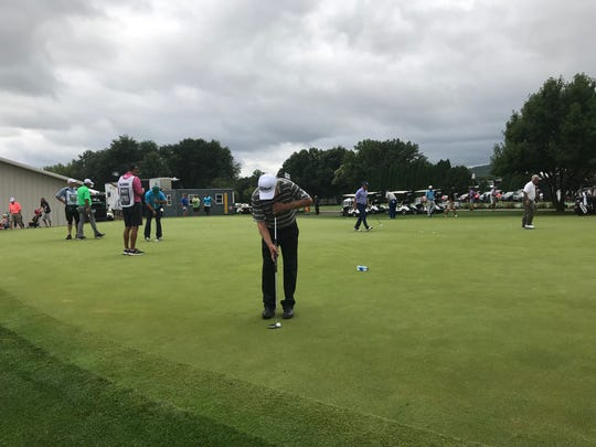 Golfers practice their putting as they wait to resume the second round of the Dick's Sporting Goods Open on Saturday.
