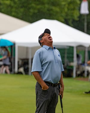 Pro golfer Mark Brooks catches rain drops on his tongue during a nearly three hour rain delay at the Dick's Sporting Goods Open on Saturday in Endicott, New York.
