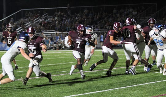 Otis Mallory blasts through the hole created by his offensive line in the fourth quarter against Enka for a 19-yard touchdown run.