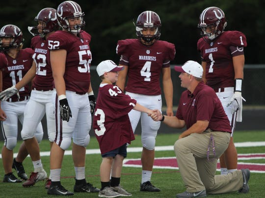 Owen head coach Nathan Padgett shakes Landon Cooper's hand before his team's 34-7 win over Enka to open the season. Padgett dedicated the victory to Cooper, who the Warhorses visited at Swannanoa Valley Montessori School in April after he wrote them a letter.