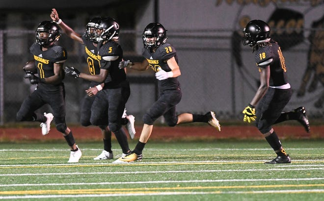 Buck Mitchell (1) and teammates celebrate Mitchell's 90 yard return for a touchdown during Friday's game against Eau Gallie.