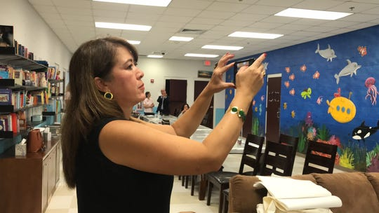 Artist Luz Cubano takes a picture of her mural in the The Ark, an assessment center and emergency shelter for youth.
