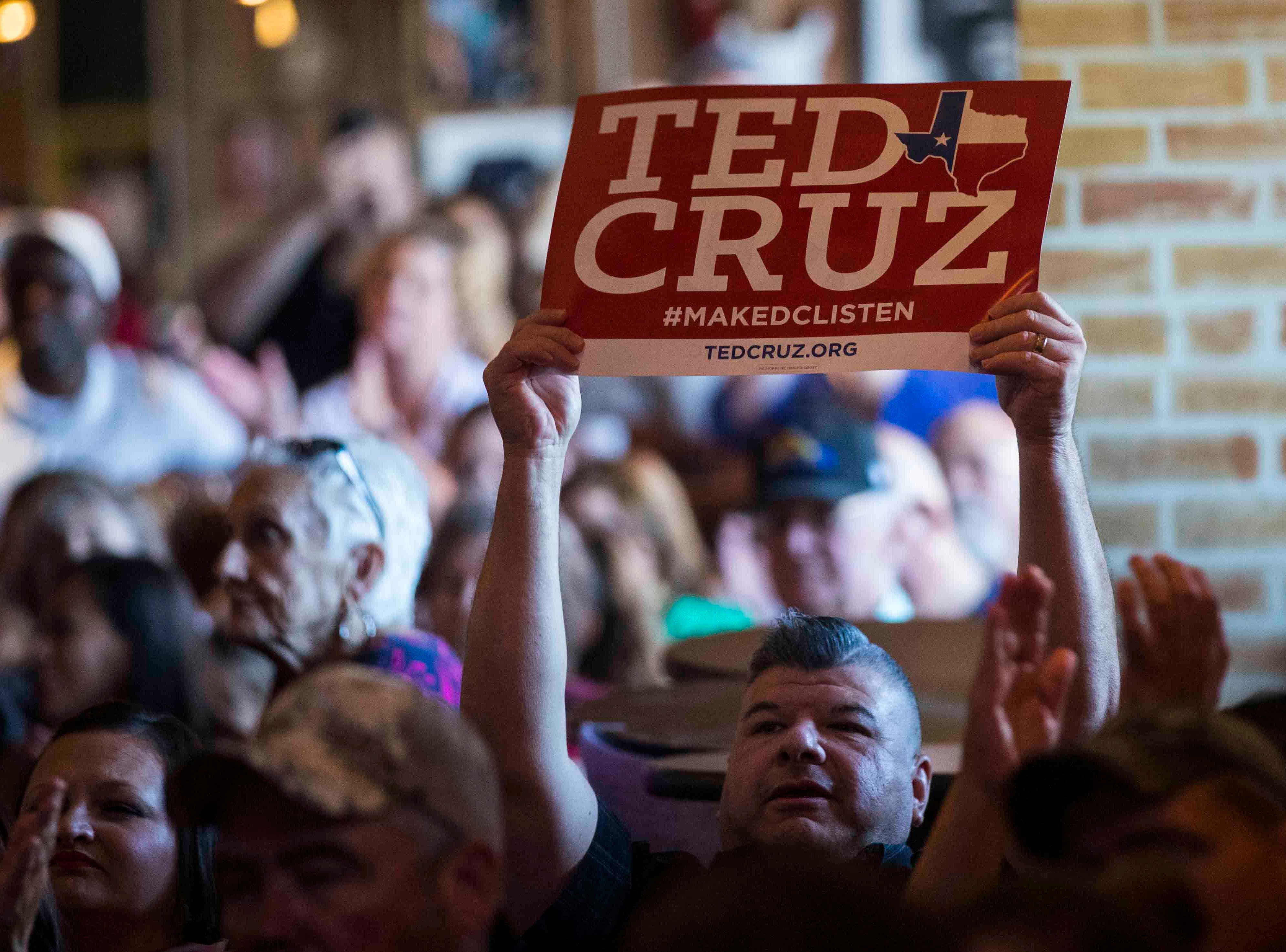 A man holds up a Ted Cruz campaign sign during an event on Saturday, August 16, 2018, at House of Rock in Corpus Christi.