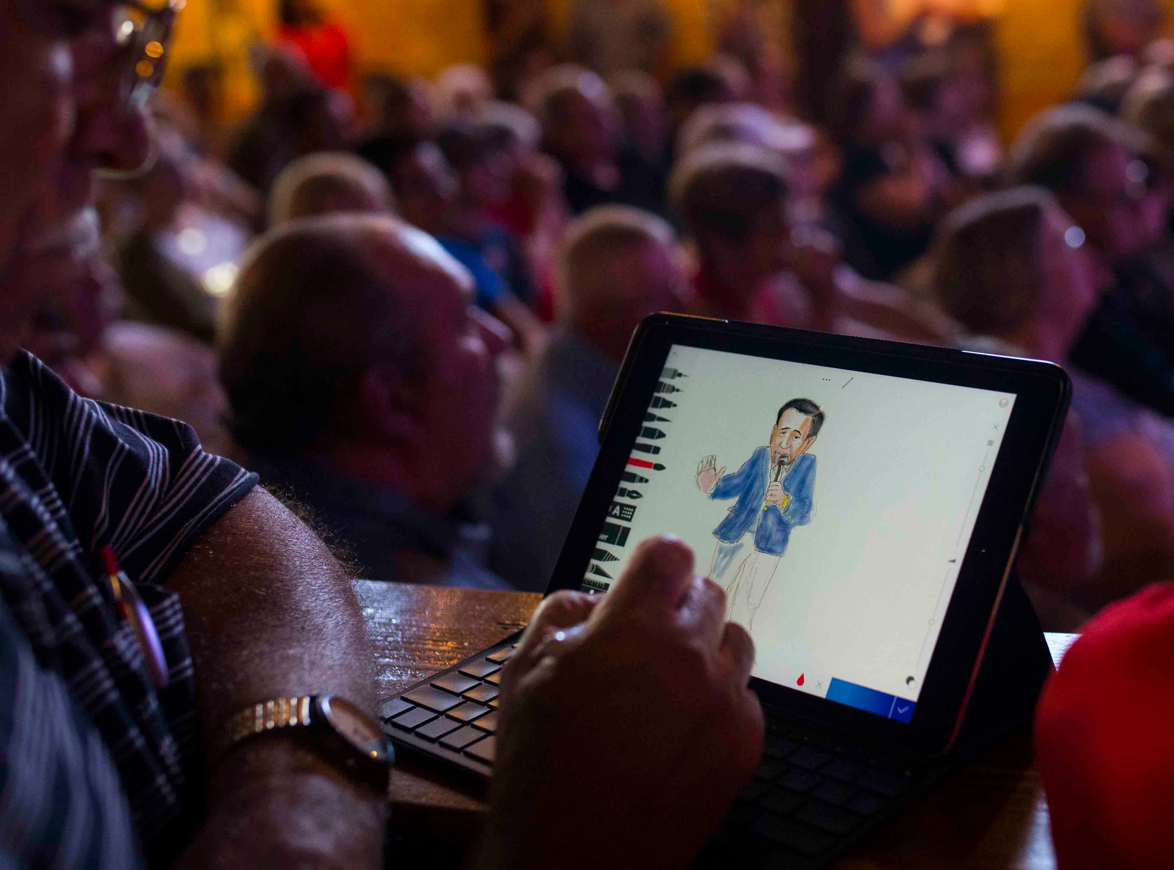 A man draws U.S. Sen. Ted Cruz as he speaks at a campaign event on Saturday, August 16, 2018, at House of Rock in Corpus Christi.