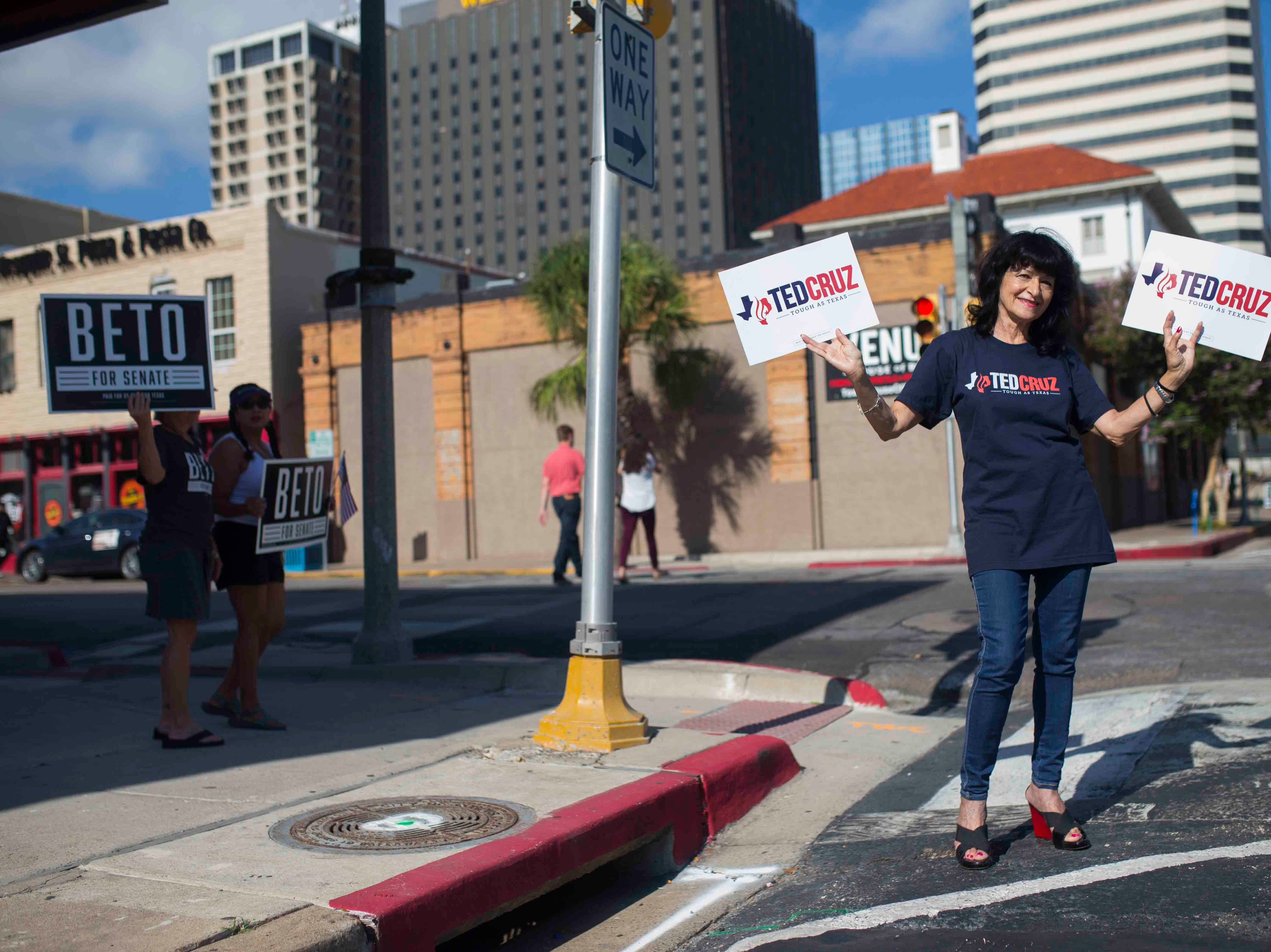 Margaret Fratila (right) stands in front of people with Beto O'Rourke signs before a Ted Cruz campaign event on Saturday, August 16, 2018, at House of Rock in Corpus Christi.