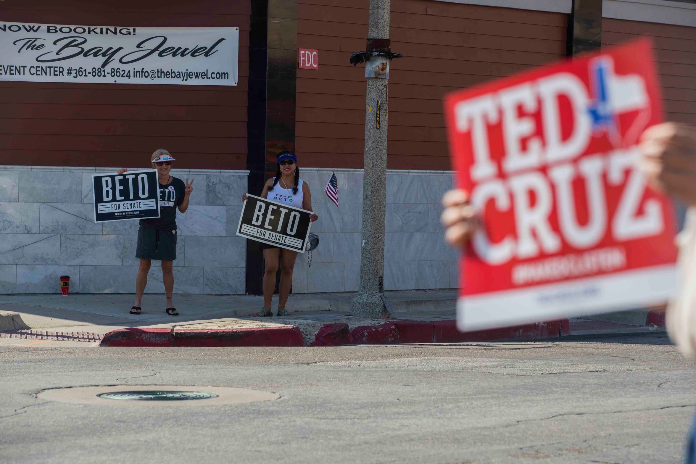 Jeanne Leonard (left) and Maria S. Olivares stand outside a Ted Cruz campaign event holding their Beto O'Rourke signs  on Saturday, August 16, 2018, at House of Rock.