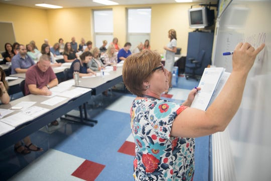 Second grade teacher Beth Hartshorn at Southeastern Local Schools writes the PAX website on the board for the other teachers to write down.