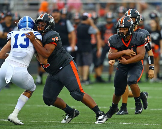 Ryle running back Wyatt Caldwell, with lineman Devon Coleman blocking, runs for a first down against Covington Catholic at the Skyline Chili Crosstown Showdown at Ryle High School. Covington Catholic defeated Ryle 40-7.