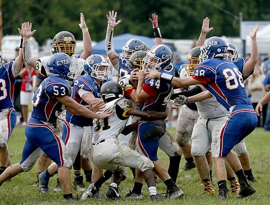 Max Boland's teammates throw up their hands as he scores a touchdown against St. Bernard-Elmwood Place during their jamboree game in Williamsburg Friday, Aug. 17, 2018. The game was played in honor of late coach Ken Osborne.