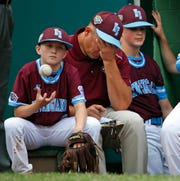 Coventry, Rhode Island's Noah McParlin, left, tosses a ball as he sits on the dugout steps with coach John Fretts, center, and Tommy Turner waiting to take the field for the top of the sixth inning of an elimination baseball game against Grandview's (Des Moines) at the Little League World Series tournament in South Williamsport, Pa., Saturday, Aug. 18, 2018. Iowa won 9-5, eliminating Rhode Island from title contention.
