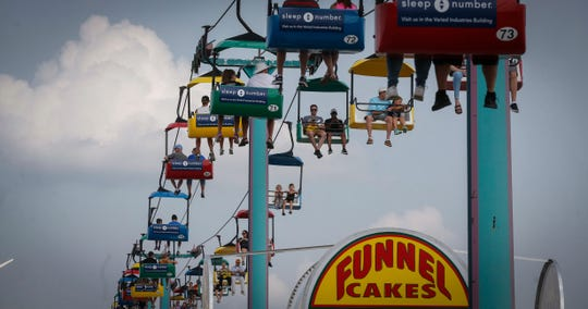 Fairgoers enjoy a ride over a funnel cake stand on Saturday, Aug. 18, 2018, at the Iowa State Fair in Des Moines.