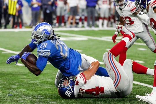 LeGarrette Blount is stopped by Giants linebacker Mark Herzlich during the second half of a preseason game.