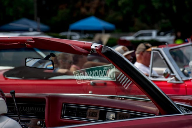A Woodward Dream Cruise commemorative license plate is reflected in the window of a 1960s Cadillac on Aug. 18, 2018.
