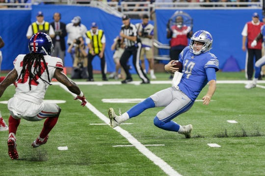 Lions quarterback Jake Rudock (14) slides in front of New York Giants defensive back B.W. Webb (37) for s second down during the first half of the preseason game against New York Giants at Ford Field in Detroit, Friday, August 17, 2018.