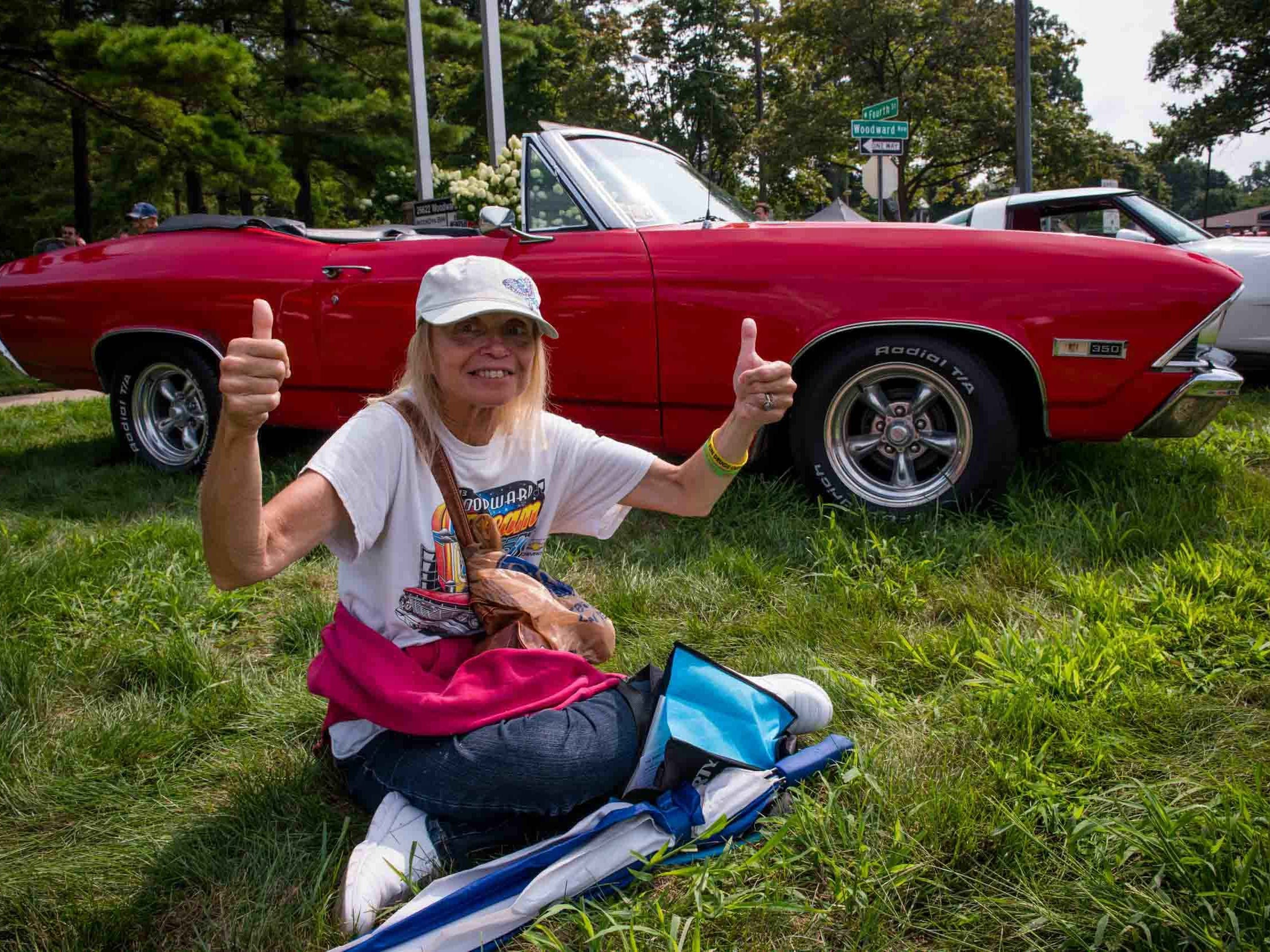 Diane Ellis of Rose gives the thumbs up to cruisers during the 2018 Woodward Dream Cruise on Aug. 18, 2018.