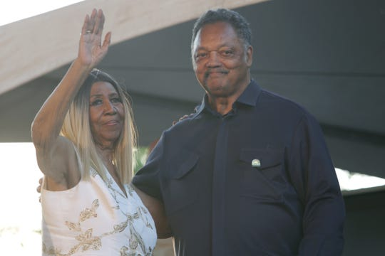 Aretha Franklin, left, and the Rev. Jesse Jackson wave to the crowd from the Madison Central stage during the Detroit Music Weekend on Saturday, June 10, 2017 in Detroit.