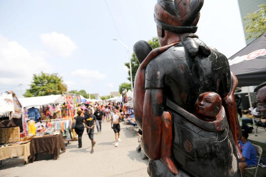 """Artwork by Bamba Thiam called """"Kumba"""" tower over festival goers as they enter the 36th Annual African World Festival at the Charles H. Wright of African-American History in Detroit on Saturday, Aug. 18, 2018."""