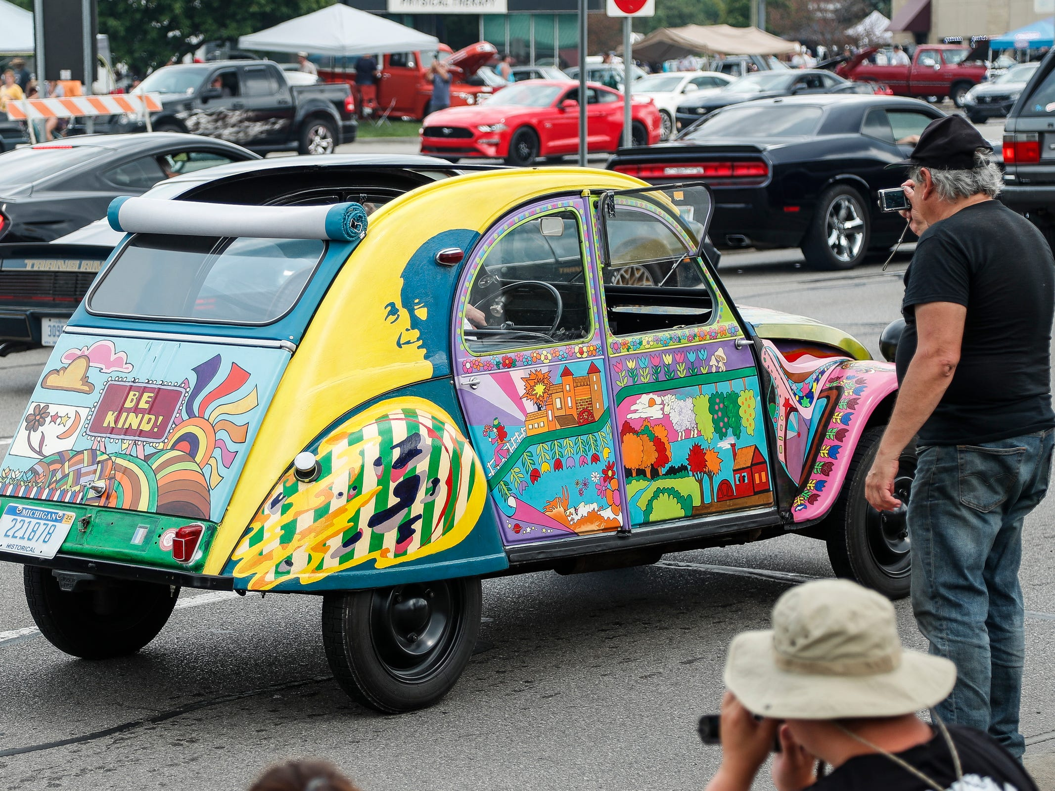 Steve Goldsmith of Long Island, N.Y., takes photos of a colorfully decorated car on Woodward Avenue in Royal Oak during the Woodward Dream Cruise, Saturday, August 18, 2018.