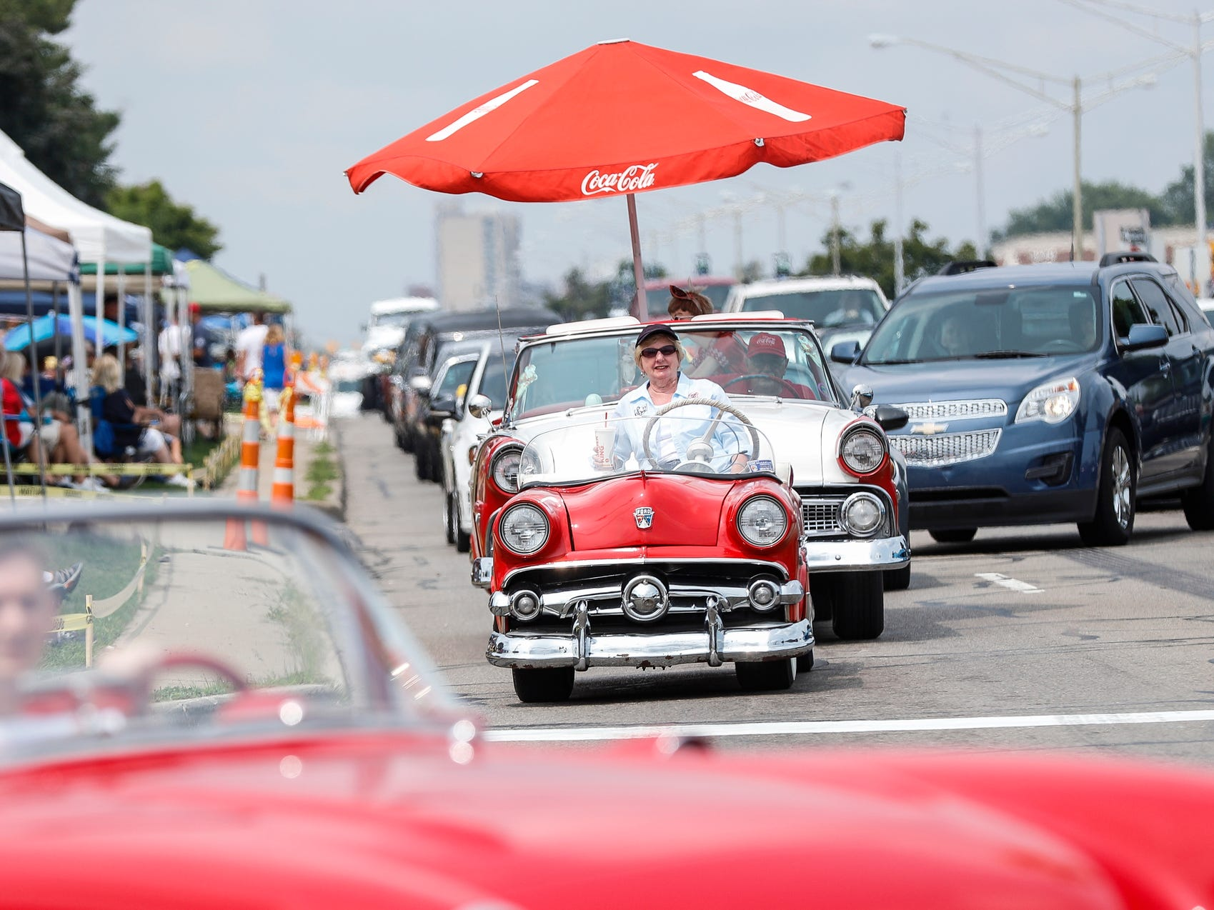 Lorraine Haas of South Lyon, center, drives a 1954 Ford replica golf cart on Woodward Avenue in Royal Oak during Woodward Dream Cruise, Saturday, August 18, 2018.